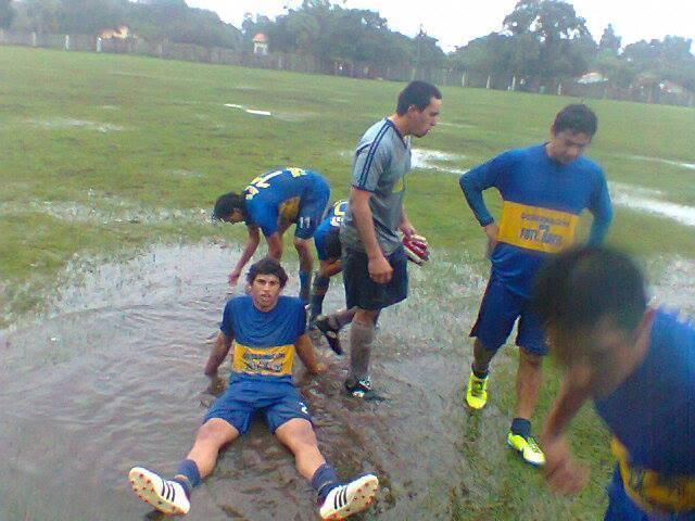 Los jugadores del Juventud de Presidente Hayes en un partido con lluvia. Las condiciones de la cancha se explican por sí sola. Muchas veces, los partidos se juegan en condiciones casi imposibles.